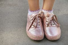 Childly legs in light pink color sneakers with glamor glitter and shoelaces royalty free stock photos