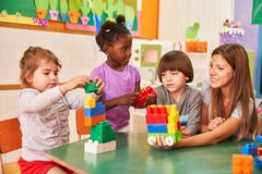 Free Childminder And Children Play With Building Blocks Stock Photography - 220751342