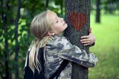 Childn som omfamnar trädet Utomhus- natur för miljöskydd Beskydd utomhus royaltyfri foto