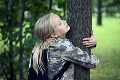 Childn som omfamnar tr?det Utomhus- natur f?r milj?skydd Beskydd utomhus arkivfoto