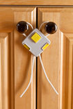 Childproof lock. Cupboard doors held safely closed from children by childproof lock Royalty Free Stock Photos