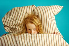Childr girl lying in bed and peeking out from under the blanket, top view. royalty free stock images