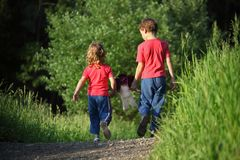 Childre go for walk with doll, rear view Royalty Free Stock Image