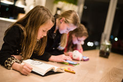 Childreen with book and ipads. One of my children still likes to read books Stock Images