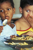 Childreen eating spaghetti, Brazil. Two children eating spaghetti with a spoon in a kindergarten in Rondonia, amazon basin, Brazil Stock Photo