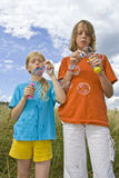 Childrem blowing bubbles. Children wearing colorful T-shirts blowing bubbles on summer meadow Royalty Free Stock Images