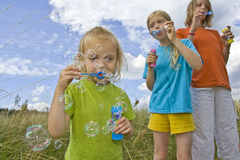 Childrem blowing bubbles. Children wearing colorful T-shirts blowing bubbles on summer meadow Royalty Free Stock Photo