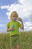 Childrem blowing bubbles. Children wearing colorful T-shirts blowing bubbles on summer meadow Royalty Free Stock Photography