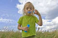 Childrem blowing bubbles. Children wearing colorful T-shirts blowing bubbles on summer meadow Stock Photos