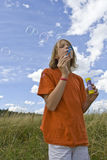 Childrem blowing bubbles. Children wearing colorful T-shirts blowing bubbles on summer meadow Stock Photography
