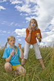 Childrem blowing bubbles. Children wearing colorful T-shirts blowing bubbles on summer meadow Stock Image