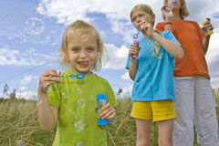 Childrem blowing bubbles. Children wearing colorful T-shirts blowing bubbles on summer meadow Royalty Free Stock Image