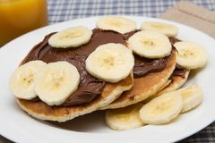 Banana pancakes with chocolate and orange juice Royalty Free Stock Images