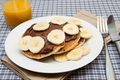 Banana pancakes with chocolate and orange juice Royalty Free Stock Photography
