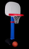 Children's Plastic Basketball Hoop with Ball. Children's plastic basketball hoop. Blue stand, gray backboard, and orange hoop. Isolated on black royalty free stock photo