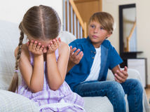 Children's quarrel indoor. Portrait of big brother and crying little sister quarreling indoors. Focus on girl Royalty Free Stock Photography
