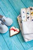 Children& x27 ενδύματα του s, παπούτσια και καρδιά μελοψωμάτων Στοκ Φωτογραφίες