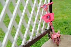 Children& x27; самокат s полагается на загородке Стоковое Изображение