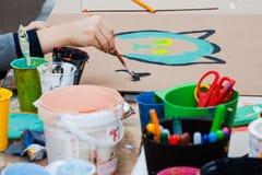 Children& x27; творческие способности s Рука рисуя краски ребенка Чонсервные банкы краски на таблице Стоковое Фото