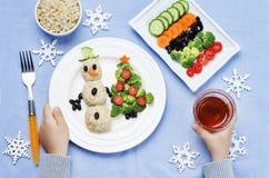Children& x27; 有圣诞节的s手与健康食物吃午餐 库存图片