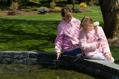 Children. A horizontal picture of two girls in pink jackets studying pond life while one girl points out something to the other girl Royalty Free Stock Photos