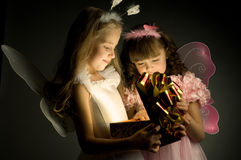 Children. Two little girl examine gift in fancy box, smile, on dark background Royalty Free Stock Photos