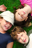 Children. Portrait of three young children lying on grass looking up royalty free stock images
