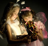 Children. Two little girl examine gift in fancy box, smile, on dark background Royalty Free Stock Photography