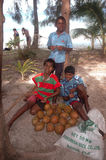 Children. Three island children on the Isle of Pines in the south Pacific, were selling coconuts to the tourist from a cruise ship, visiting their island for Stock Image