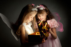 Children. Two little girl examine gift in fancy box, smile, on dark background Stock Images