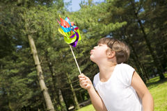 Children. Young girl in park blowing on pinwheel Stock Images