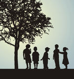 Children. In a confidential interview under a tree Royalty Free Stock Images