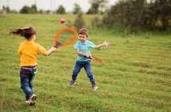 Free Children - A Boy In A Blue T-shirt And A Girl In Yellow Play Tennis With Rackets And A Ball On Nature Royalty Free Stock Photos - 173928518