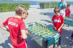 Children, adolescents, play table football on the Volga River Embankment on a sunny summer day. Russia, Samara, August, 2018: children, adolescents, play table royalty free stock photography