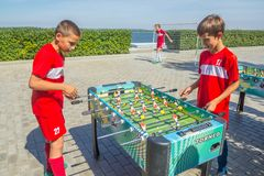 Children, adolescents, play table football on the Volga River Embankment on a sunny summer day. Russia, Samara, August, 2018: children, adolescents, play table stock photography