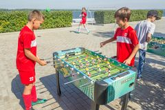 Children, adolescents, play table football on the Volga River Embankment on a sunny summer day. Russia, Samara, August, 2018: children, adolescents, play table stock images