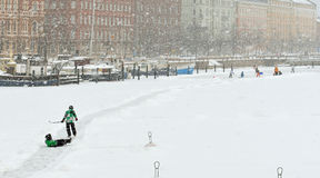 Children and adults in any weather skate on ice in Northern harbor Royalty Free Stock Image