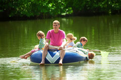 Children and adults float on an inflatable boat Stock Image