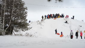 Children and adults glide on the snow tubing. Yegoryevsk, Moscow Region, RUSSIA - JAN 17, 2016: Kids climb on tubing slope with tubes in hands for downhill stock video footage