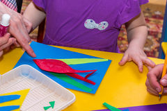 Children and adults hands glue colored paper on application mast Stock Photos