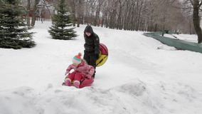Children and adults on an inflatable sled and tube. Icy snowy hill. Tubing. Russia, city of Saratov, 10 Jan. 2017.  stock footage