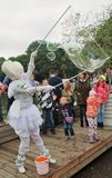 Children and adults watch in admiration at soap bubble maker Royalty Free Stock Photo