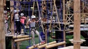 Children age 6-12 attend indoor adventure climbing park stock video