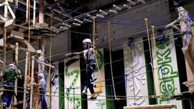 Children age 6-12 attend indoor adventure climbing park stock video footage