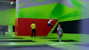 Children age 10-12 jumping on trampoline in a mall stock video footage
