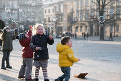 Children age 4-5 years playing with soap bubbles on the square Stock Photos