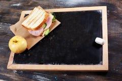 Children& x27; almoço de s à administração da escola, giz, um espaço para a inscrição, maçã, sanduíche Imagens de Stock