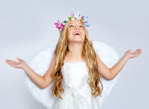 Children angel girl looking up sky with open hands. Angel children girl with white wings and flowers crown Royalty Free Stock Photography