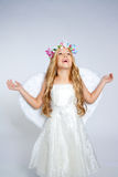 Children angel girl looking up sky with open hands. Angel children girl with white wings and flowers crown Stock Photography
