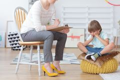 Children anxiety and depression concept. Psychologist talking with sad little boy at the office stock images